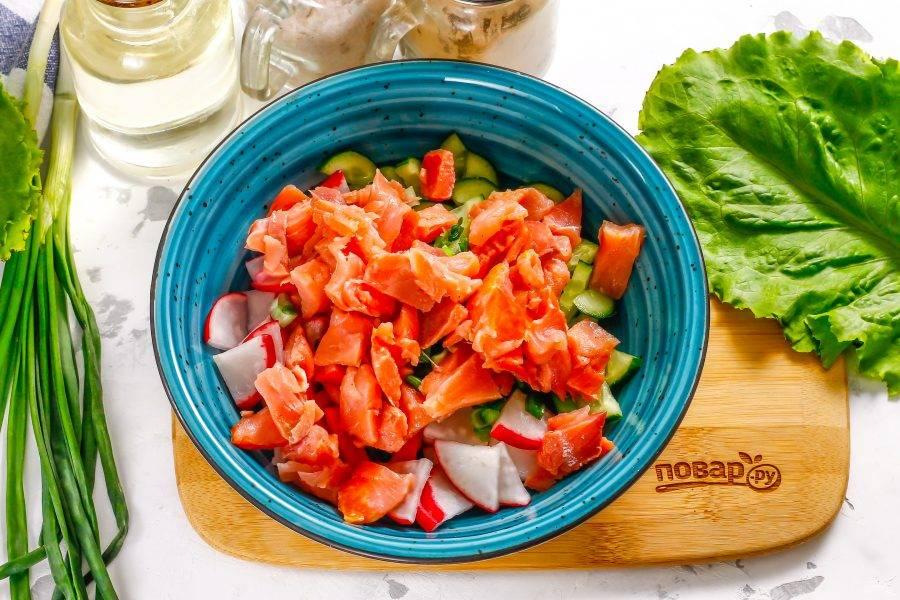 Слабосоленую красную рыбу любого сорта очистите от косточек, нарежьте небольшими ломтиками и добавьте в емкость.