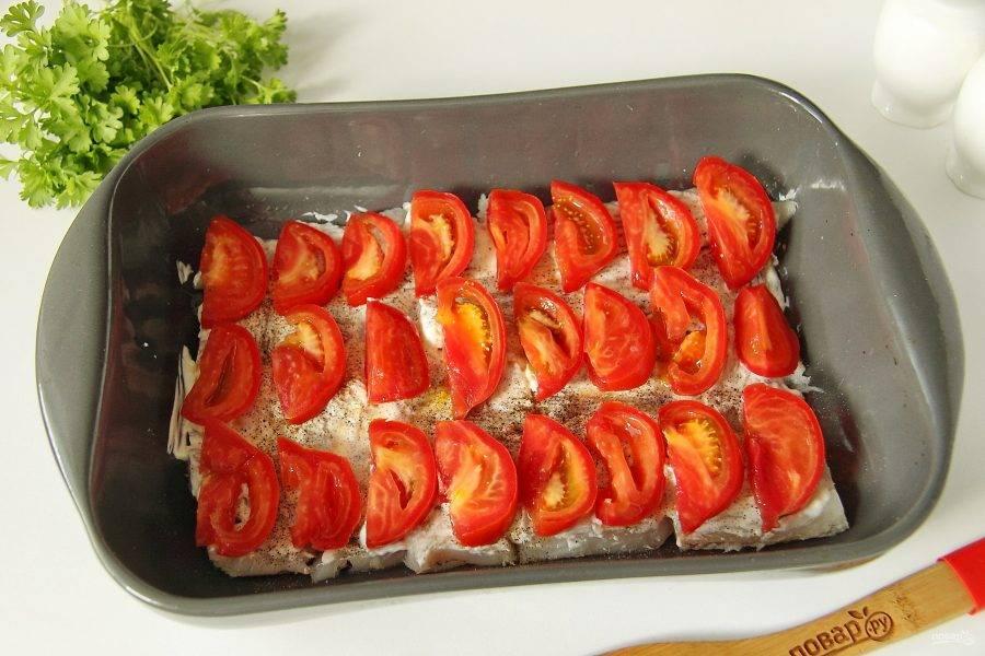 Выложите на филе нарезанные дольками помидоры.