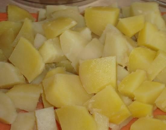 Картошку в мундире тоже до полуготовности отварите. Потом почистите и нарежьте кубиками.