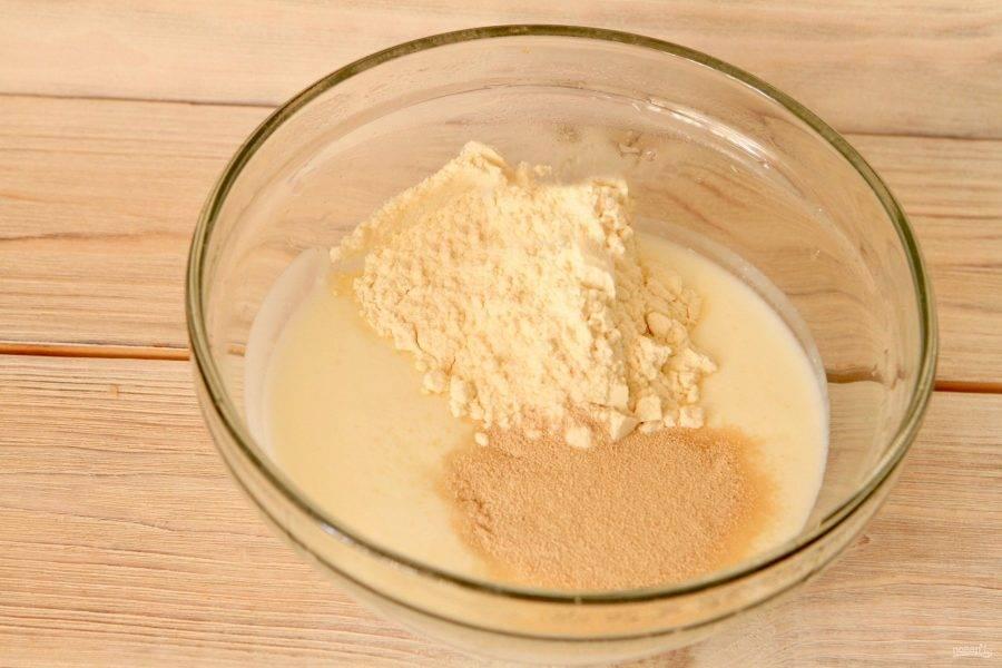 В миску просейте муку, влейте половину кефира (комнатной температуры), добавьте дрожжи и сахар. Тщательно перемешайте массу до однородности.