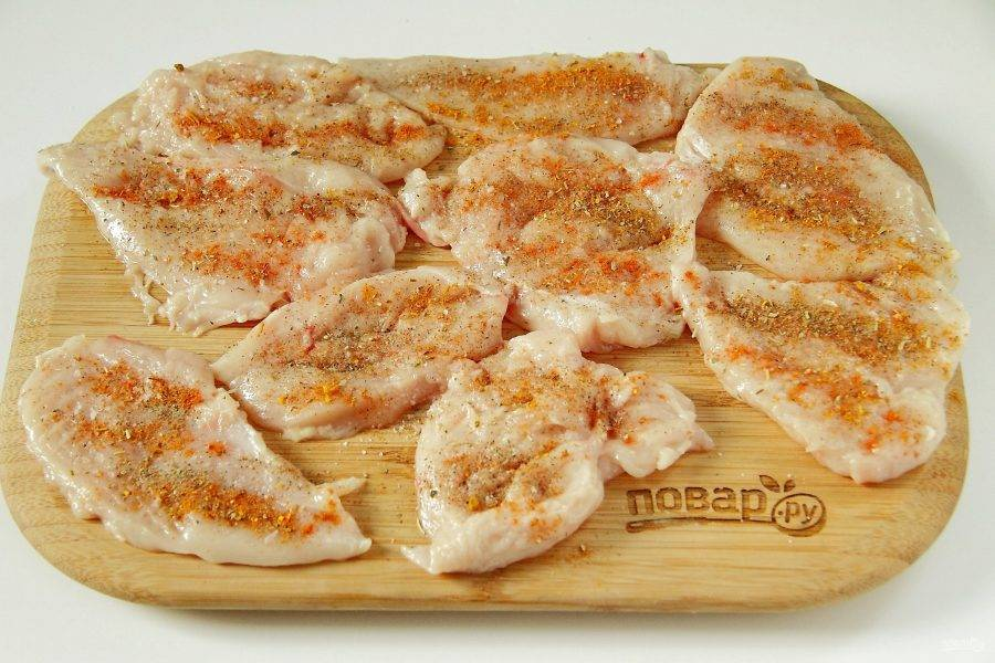 Куриную грудку промойте, обсушите бумажным полотенцем и нарежьте вдоль на необходимое количество порций. Отбейте кусочки с двух сторон специальным молоточком, затем посыпьте солью и специями.