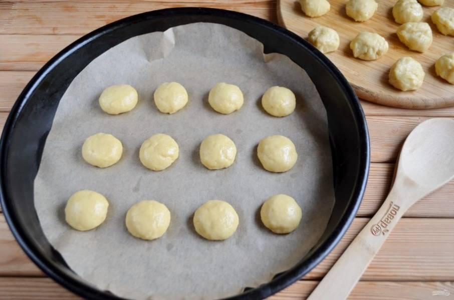 Разделите тесто на 40 кусочков. Скатайте кусочки в шарики. Разложите на пекарской бумаге их на расстоянии друг от друга. Чуть придавите, чтобы получились полусферы. Прогрейте духовку до 180 градусов.