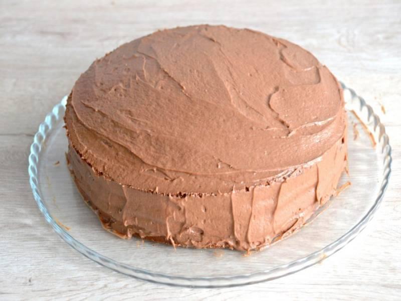 Смажьте кремом верх и бока торта.