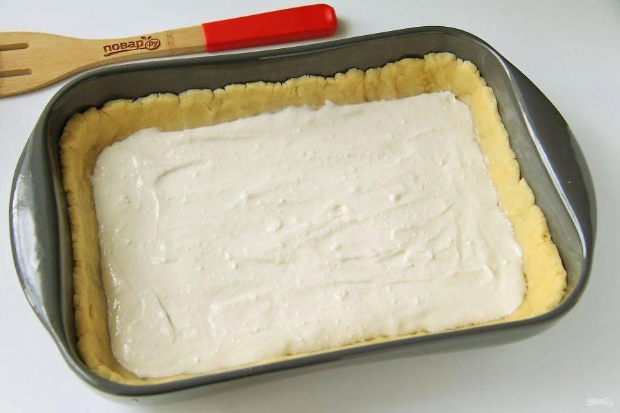 Распределите тесто по смазанной маслом форме, формируя руками высокие бортики. Смажьте дно и бока 2 ложками белка (еще не взбитого), затем сверху выложите творожную начинку.