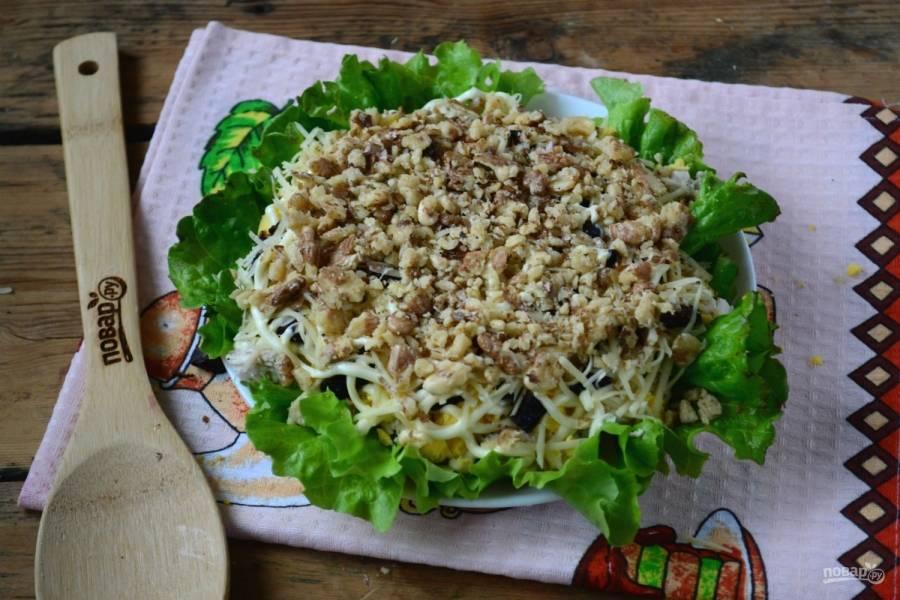 Грецкие орехи измельчите в блендере или растолчите в ступке. Выложите на салат и смажьте майонезом.