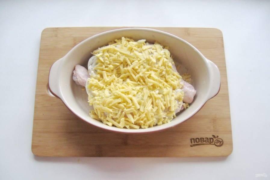 Посыпьте окорочка тертым сыром. Налейте в форму 100-150 мл. бульона или воды.