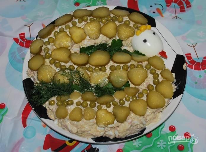 Украшаем верхушку салата порезанным солеными огурцами и зеленью. Приятного аппетита!