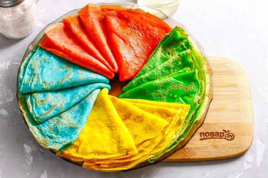 Горячие блины сверните в два раза и выложите на тарелку.