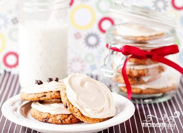 4. Чтобы сделать глазурь, нагреть молоко, добавить кофе и дать настояться в течение 5-10 минут. Процедить смесь. Дать остыть до комнатной температуры около 15 минут. В средней миске взбить сливочное масло до кремовой консистенции. Добавить половину сахара и взбить. Перемешать с ванильным экстрактом и половиной кофейной смеси. Добавить оставшийся сахар и взбить. Размешать с оставшейся кофейной смесью и тщательно взбить. Залить остывшее печенье глазурью. При желании украсить сверху шоколадными чипсами.