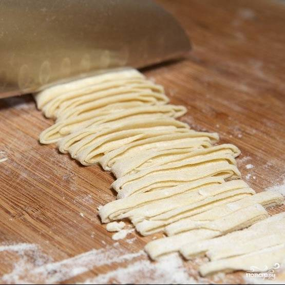 При помощи острого ножа разрезаем тесто на тонкие полоски.