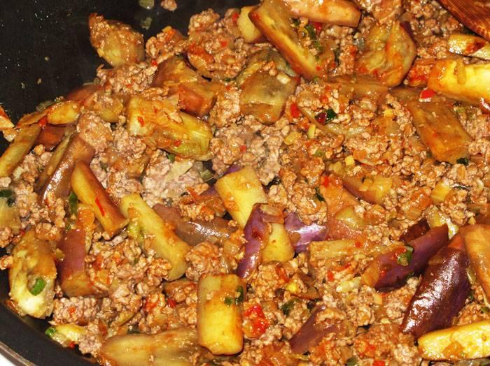 Добавляем к луку фарш, солим и перчим, добавляем чили и обжариваем минут 7. Потом добавляем баклажаны и кунжутное масло, жарим до тех пор, пока баклажаны не станут мягкими.