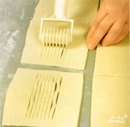 2.Размороженное тесто раскатываем толщиной 5 миллиметров, разрезаем его на квадраты размером примерно 15х15 сантиметров. Специальным или обычным кухонным ножом делаем надрезы в центре половины всех квадратов.
