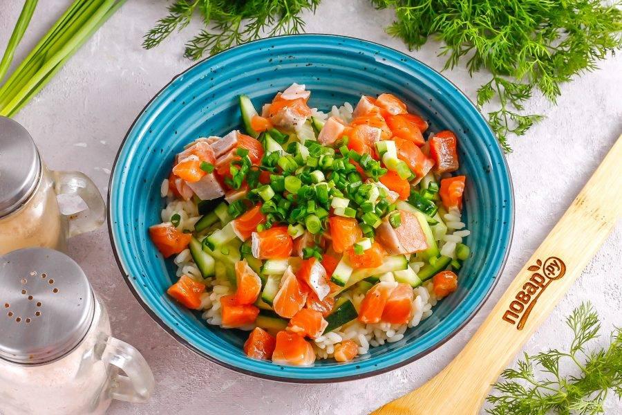 Удалите из рыбы косточки, если они присутствуют. Нарежьте ее кубиками и добавьте в емкость. Промойте стебли зеленого лука, измельчите и всыпьте к рыбной нарезке.