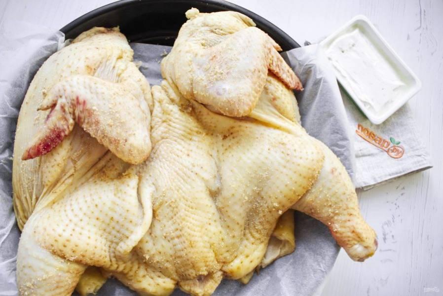 Курицу разрежьте по грудке и разверните, как на фото. Натрите сушенным чесноком. Поместите курицу на противень с пергаментом для выпечки.