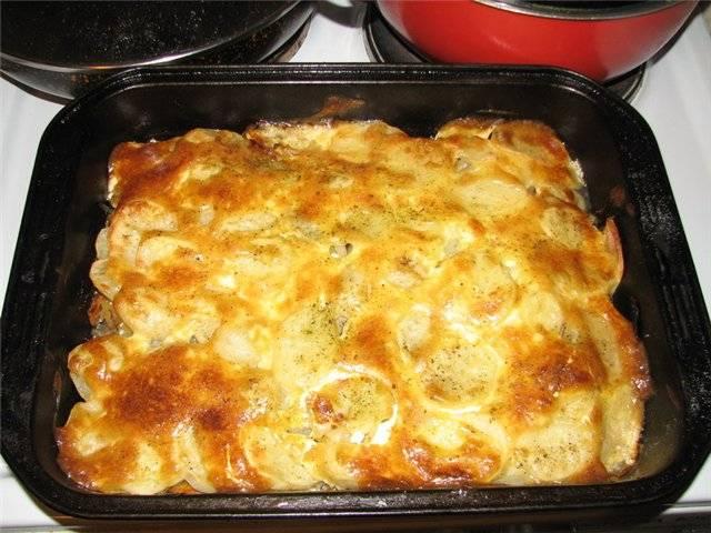 Картофель нарезаем колечками, выкладываем на овощи по всей поверхности. Солим и перчим, затем обильно смазываем майонезом. Ставим в прогретую до 200 градусов духовку. Запекаем до готовности.