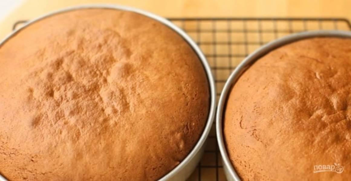 2. Добавьте муку с содой ко взбитым яйцам, перемешайте лопаткой до однородности. Разделите тесто на две части. Формы для выпечки застелите пергаментом, распределите в них тесто.