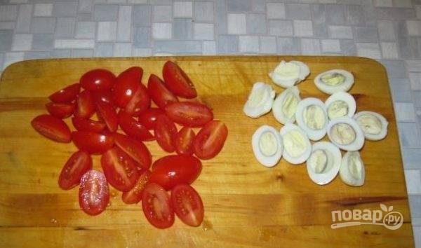 Нарезаем помидоры черри и очищенные яйца на небольшие ломтики и выкладываем в миску к креветкам.