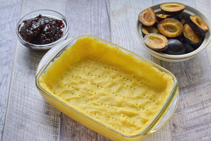 Большую часть теста распределите по дну и бортикам формы для запекания (19х14 см), наколите тесто вилкой.