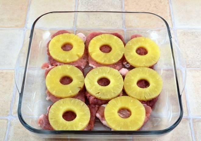В смазанную маслом форму выложите кусочки свинины. На каждый положите по кольцу ананаса.