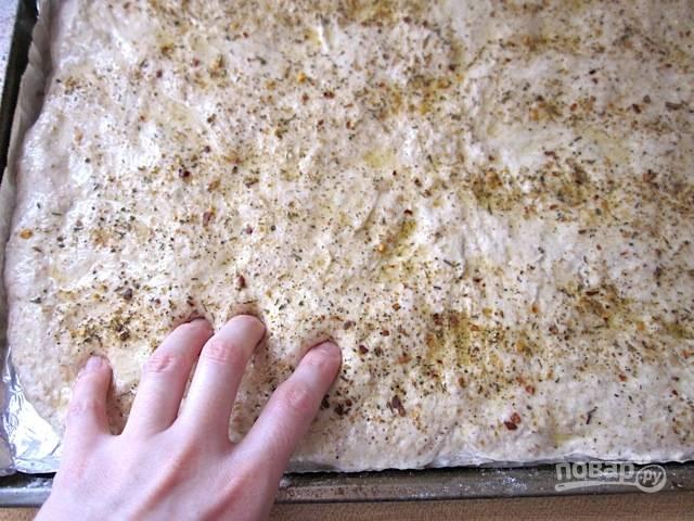 6.Вылейте на тесто 2 столовые ложки растительного масла и размажьте его кисточкой. Посыпьте итальянскими специями и оставьте на 1 час, затем пальцами сделайте ямочки по всему тесту.