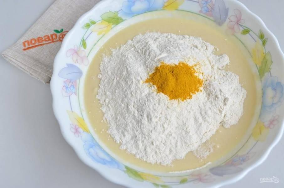 5. Всыпьте часть муки, куркуму и начните замешивать тесто, сначала ложкой, потом руками на столе.