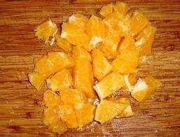 Промываем апельсин и зелень. С апельсина снимаем кожуру, удаляем белые соединительные плёнки и разделяем его на дольки. Дольки можно разрезать пополам или оставить как есть, если апельсин не крупный.