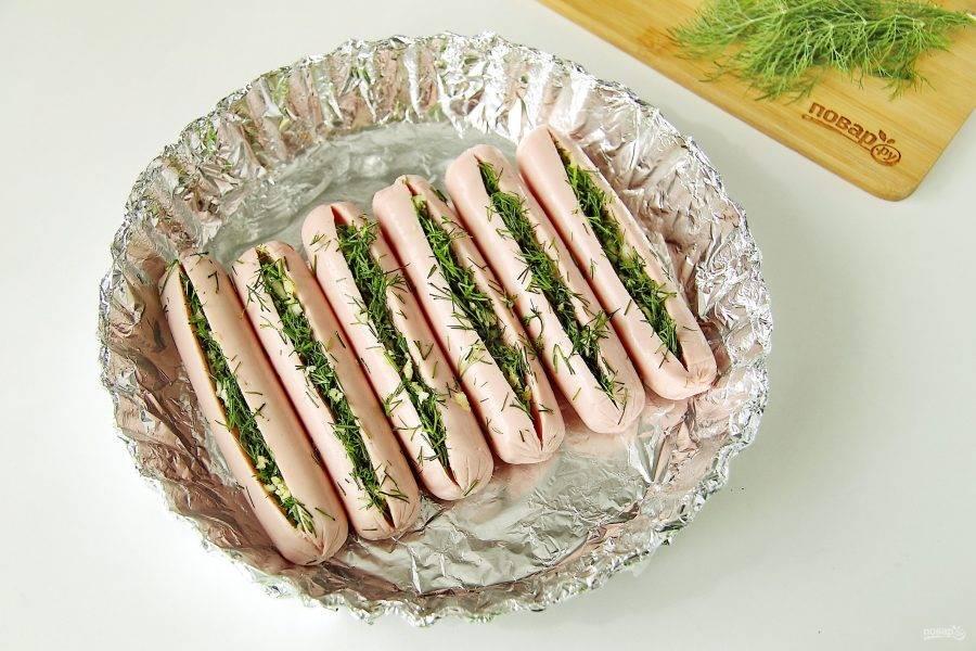 Сосиски надрежьте вдоль и нашпигуйте их зеленью с чесноком. Выложите сосиски в смазанную маслом форму для запекания.