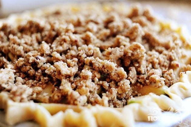 4. В миске кухонного комбайна (или вручную) смешать сливочное масло, муку, сахар, орехи пекан (измельчите их, если вы не используете кухонный комбайн) и соль. Выложить полученную смесь поверх яблок.