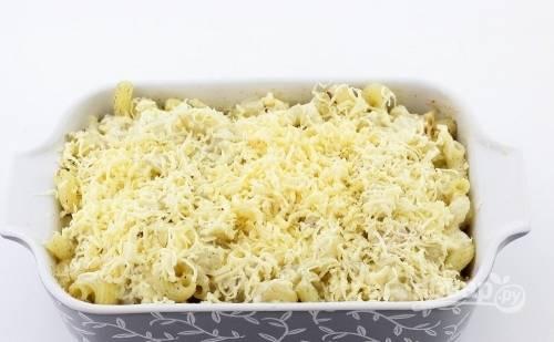 Засыпьте запеканку сыром. Духовку разогрейте до 180 градусов.