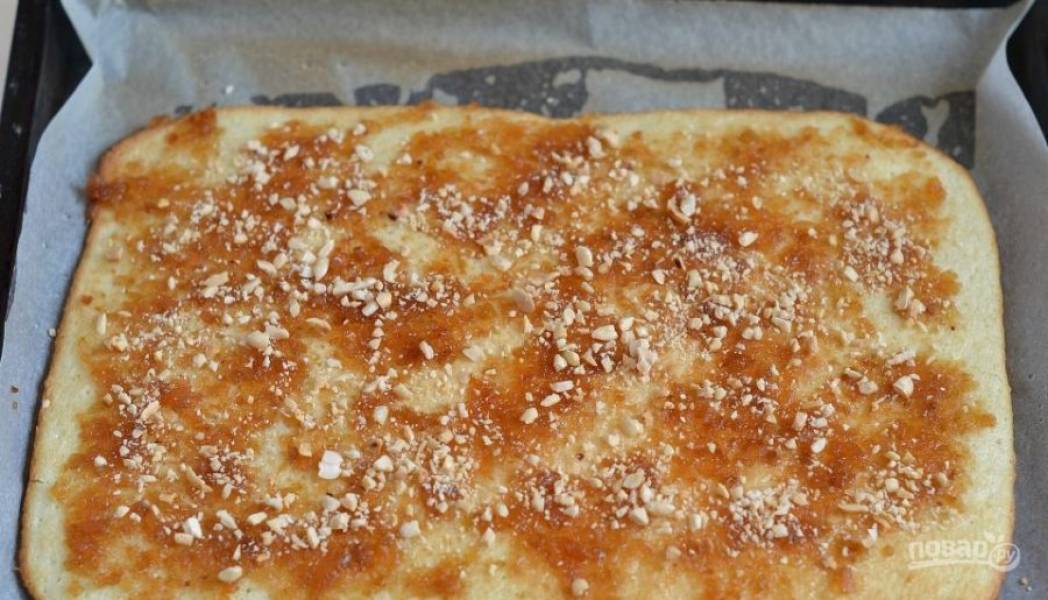 Готовый бисквит достаньте из духовки, остудите. Выложите на него яблочное повидло и распределите его по всему бисквиту. Затем присыпьте все дроблеными орешками.