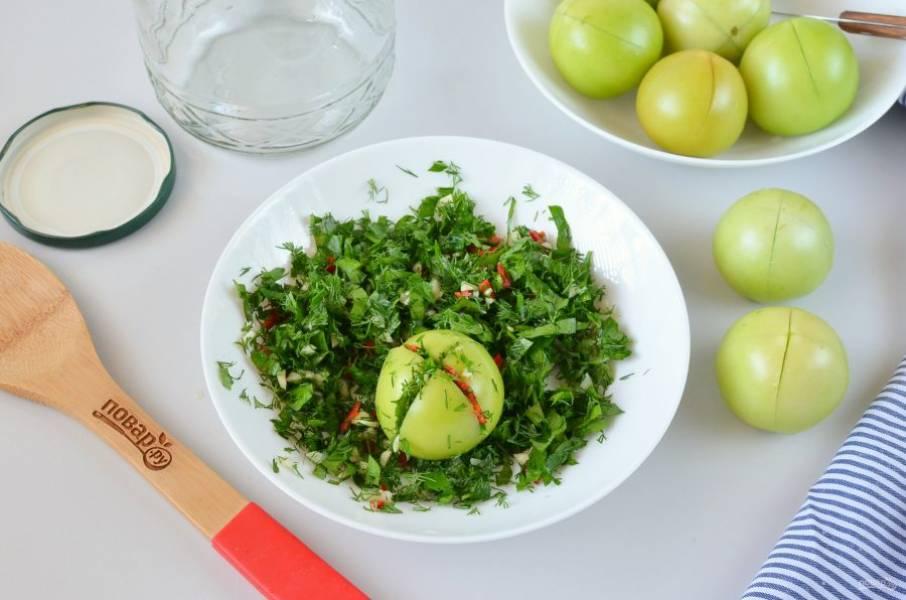 Вымойте помидоры, острым ножом сделайте крестообразный разрез не до конца. В надрезы вложите начинку из чеснока и зелени.