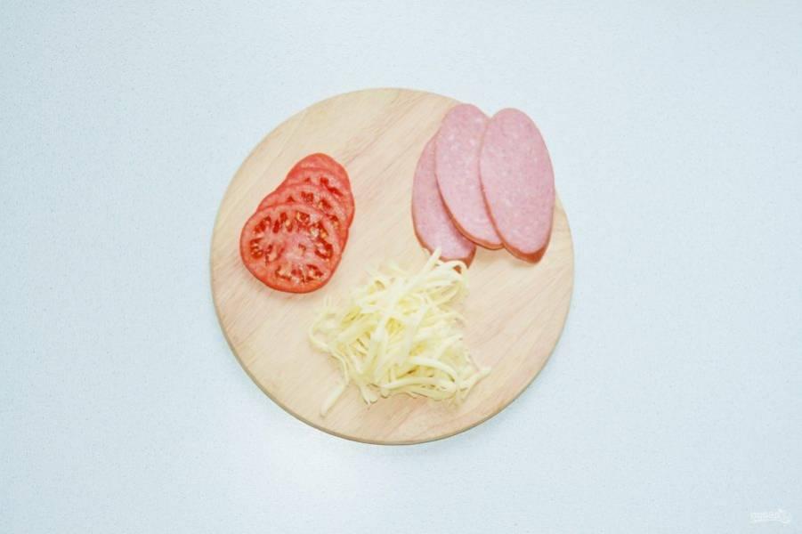 Нарежьте тонко помидоры, сыр натрите на терке. В начинку я решила добавить дополнительно несколько ломтиков колбаски.