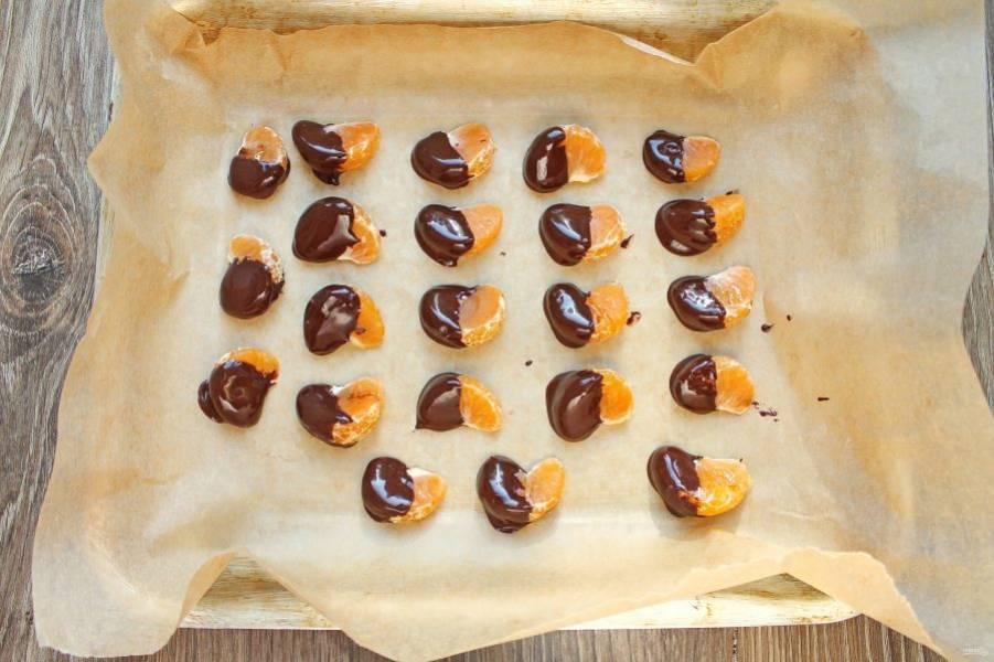 Шоколад растопите на водяной бане и обмакните одну сторону каждой дольки мандарина. Выложите в один слой на пергамент.