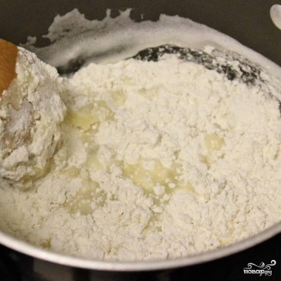 1. Плиту включите нагреваться на 200 градусов. Застелите противень пергаментной бумагой. Муку, воду и сливочное масло доведите до кипения, помешивая. Муку засыпьте сразу всю.