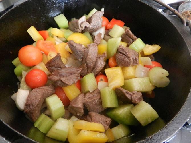 4. В сотейник к мясу отправить все овощи. Обжарить слегка и залить горячим бульоном. Накрыть крышкой и варить на среднем огне минимум 25 минут.