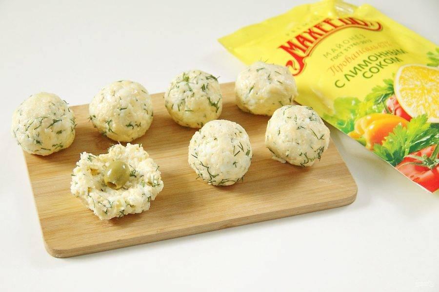 Возьмите немного сырной массы, придайте ей форму небольшой лепешки и положите по центру оливку. Сформируйте шарик, запечатав начинку внутри. Таким образом сформируйте все сырные шарики.