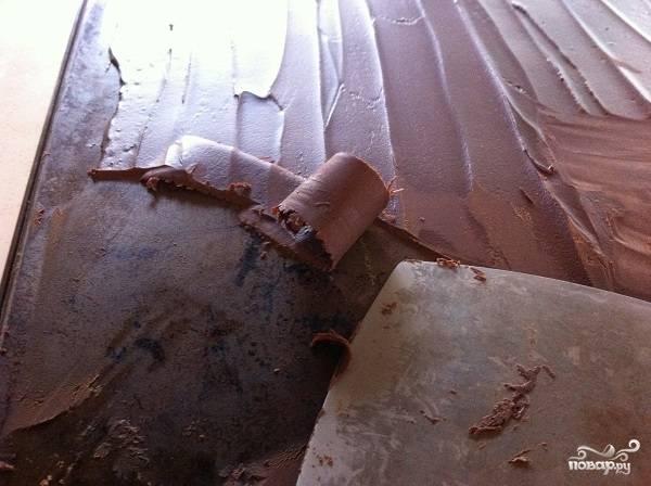 13. Украшать мы его будем свежими ягодами и шоколадом. Да-да, шоколадом. Достаньте противень из холодильника и аккуратно снимайте шоколад небольшими полосочками, которые будут вот так закручиваться.