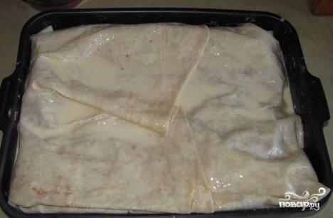 Закройте краями одного лаваша верхнюю часть пирога, щедро смажьте кефиром с яйцами, старайтесь не оставлять сухих мест. Половину оставшегося фарша выкладывайте на лаваш. Такую же процедуру повторите со следующим лавашем. Финальный слой, который закрывает пирог, полейте остатками кефирно-яичной смеси.