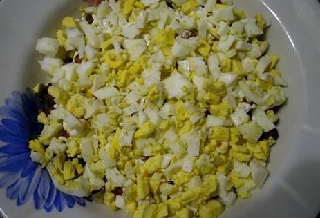 Яйца отвариваем вкрутую и нарезаем мелко, выкладываем их на грибы и смазываем майонезом.