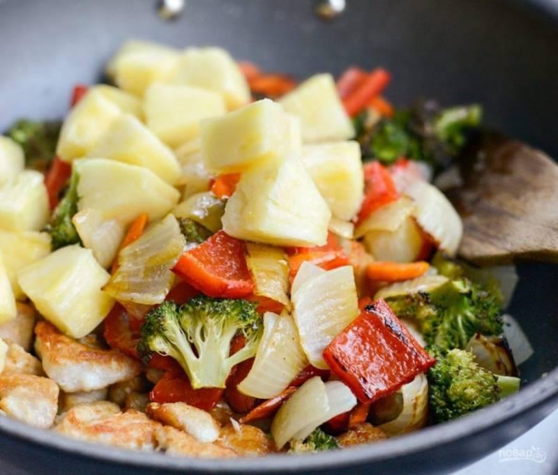 Затем в сковороду добавьте ананас кубиками, овощи из духовки и соус.