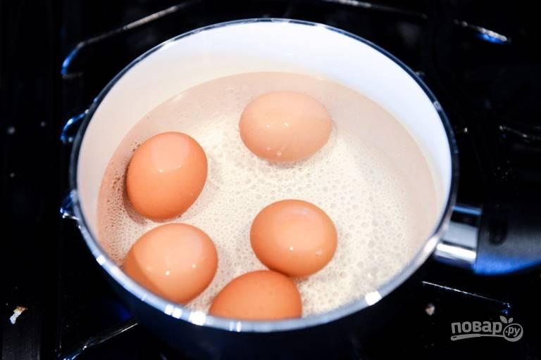 2. Яйца аккуратно промойте под проточной водой. После закипания уберите огонь и выложите яйца. Варите ровно 5.5 минут. Параллельно подготовьте небольшую емкость с водой и льдом.