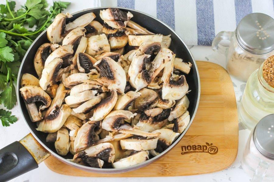 Промойте свежие шампиньоны в воде, нарежьте их слайсами. Прогрейте 1 ст.л. растительного масла на сковороде, добавьте в емкость грибную нарезку, посолите. Обжарьте в течение 4-5 минут. Остудите.