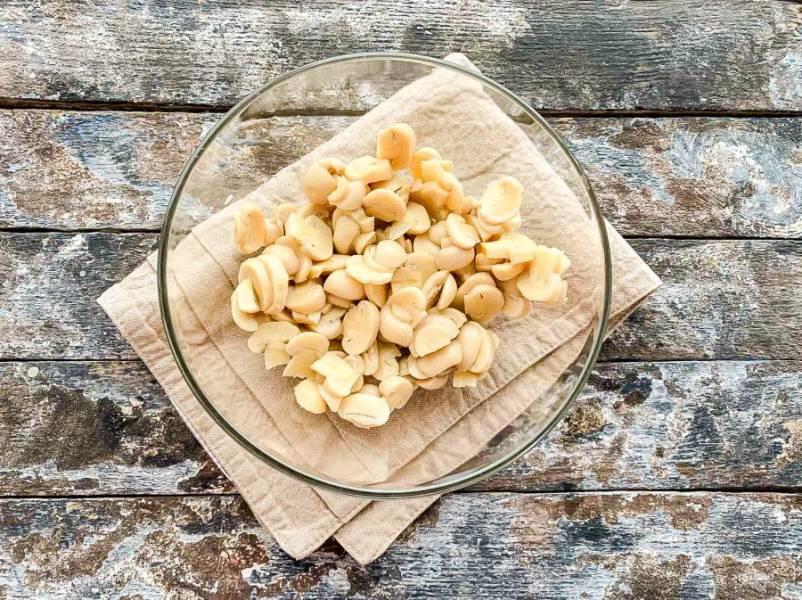 Маринованные грибы нарежьте и выложите в глубокую тарелку.