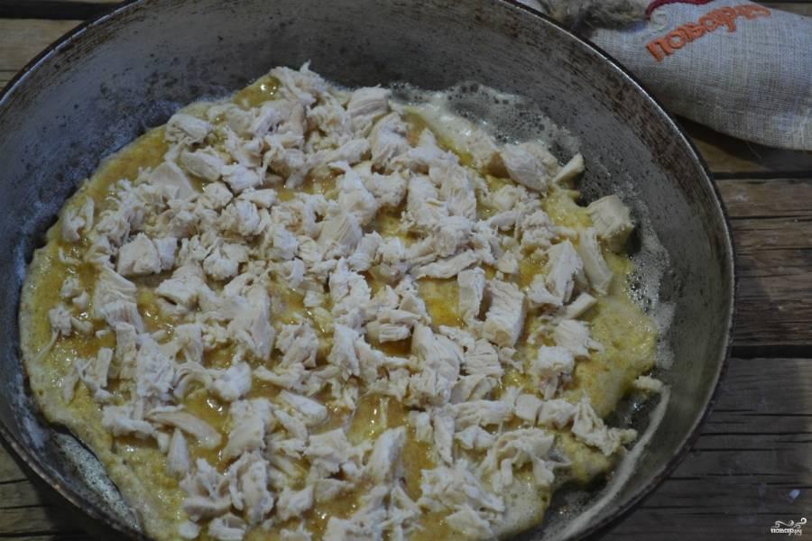 Хорошенько разогрейте сковороду, вылейте на нее тесто. Жарьте примерно 2-3 минуты. Как только снизу корж хорошенько схватится, выложите сверху измельченную курицу.