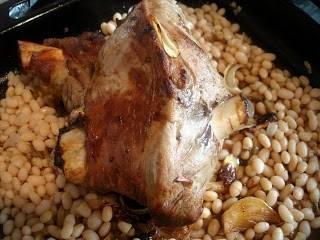 Через 30 минут интенсивного запекания ваша баранина станет румяной, этот предварительный процесс тепловой обработки нужен для того чтобы поверхность мяса покрылось плотной корочкой, которая будет удерживать мясной сок внутри, пропитывая всю мякоть. По истечению нужного времени, помогая себе кухонным полотенцем, удалите противень с бараньей ногой из духовки и уменьшите ее температуру до 175 – 180 градусов Цельсия. Затем добавьте на противень отваренную фасоль, разложив ее равномерным слоем по всему периметру и влейте 1 стакан чистой дистиллированной воды, для того чтобы во время запекания фасоль не пересохла.