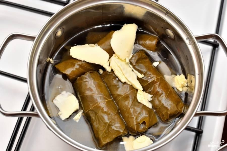 Выложите долму в кастрюлю, к ним добавьте сливочного масла. Варите около 10-15 минут. Подаётся долма с ломтиками лимона.