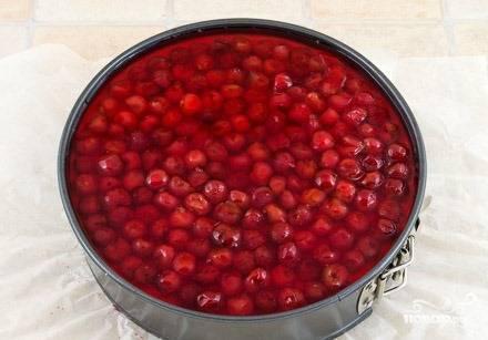 Выложите сверху застывшей творожной массы вишни, отделив их от косточки. Если вы брали замороженные ягоды, то перед этим их следует разморозить. Затем разведите пакетик с желе так, как этого требует инструкция, добавьте в него сахар, перемешивая до полного растворения. Залейте полученной смесью вишни — и снова поставьте торт в холодильник на пару часов.