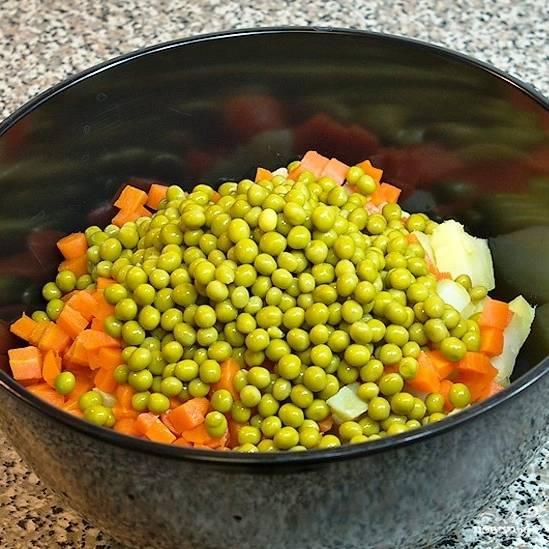 Туда же, в салатницу, добавляем горошек (без жидкости, естественно).