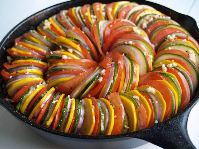 5. Температуру духовки понизьте до 135 градусов. Нарезанные помидоры, цуккини, баклажан и патиссон выкладывайте в сковороду с овощами внахлест по кругу, чередуя цвета. Сверху посыпьте выложенные овощи оставшимся измельченным чесноком, маслом, добавьте листик тимьяна.