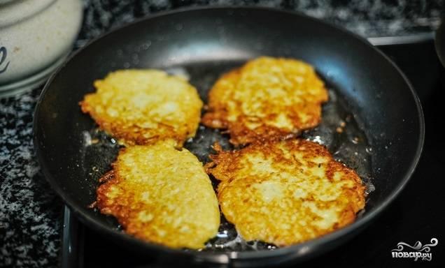 6. На сковороде разогрейте растительное масло. Ложкой выкладывайте картофель, формируя тоненькие оладьи. Жарьте их на среднем огне до румяности с двух сторон.